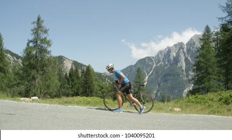Defeated by the steep mountain road, disappointed pro cyclist walks along his road bicycle. Active man training in the mountains gave up and started walking instead of cycling up steep mountain pass.