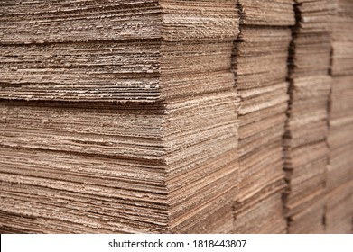 Defective corrugated sheets lie on top of each other in the printing industry. The edges of the cardboard are badly cut so it is defective. The cardboard will be sent for recycling