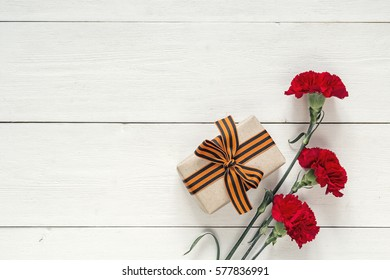 Defender of the Fatherland Day. Red carnations and gift box with st george ribbons on the white background. Space for text.