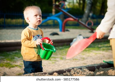 Defenseles, frightened little one year old boy is looking with fear at the the older aggressive child who wants take control. Quarrels children in the sandbox predomination of older  over the younger.