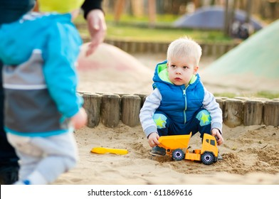 Defenseless, frightened little two years old boy is looking with fear at the the older aggressive child who wants take control.  Social situations in the sandbox