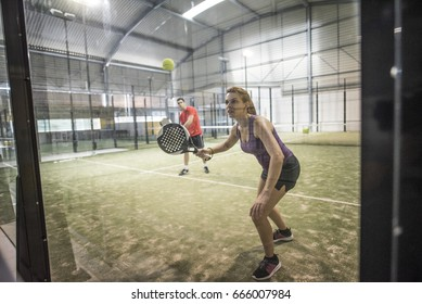 Defensive action in paddle tennis bouncing ball against crystal
