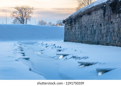 Defensive moat and wall of Daugavpils fortress in winter frost in the evening after sunset