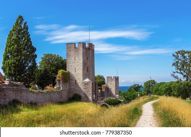 The defensive wall of Visby, Gotland in Sweden. The strongest and best preserved medieval city wall in Scandinavia. Beautiful view. Angular watchtowers and footpath along them. Blue sea on background.