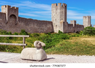 The defensive wall of Visby, Gotland in Sweden. The strongest and best preserved medieval city wall in Scandinavia. Beautiful view. Watchtowers and concrete sheep as barrier on the way to the bridge.
