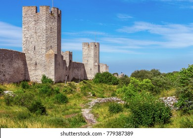 The defensive wall of Visby, Gotland in Sweden. The strongest and best preserved medieval city wall in Scandinavia. Beautiful view. Angular watchtowers and footpath along them on green meadow.