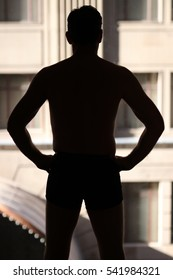 Defiant silhouette male figure looking out window over city skyline buildings
