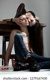 Defiantly dressed sexy brunette girl lays on the wooden table her hair is hanging down on the guy in jeans with naked torso with tattoos sitting on the floor. Cocky lovers