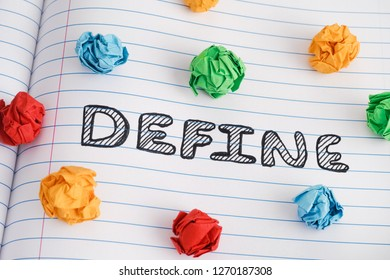 Define. Define word on notebook sheet with some colorful crumpled paper balls on it. Close up.
