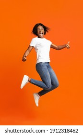 Definitely recommend it. Emotional young black woman jumping in the air and screaming, showing thumbs up, happy african american lady expressing positive emotions on orange studio background