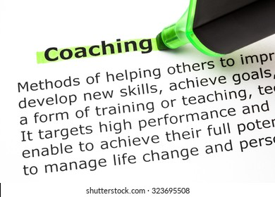 Definition of the word Coaching printed on paper and highlighted with green text marker.