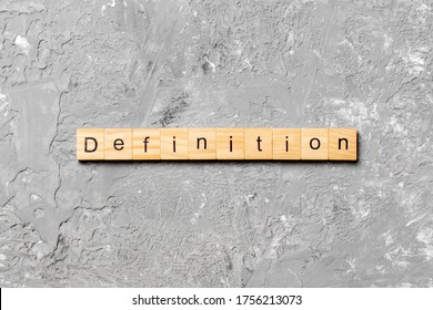 Definition word written on wood block. Definition text on cement table for your desing, concept.