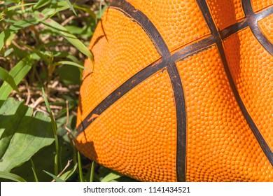 Deflated basketball laying on grass.
