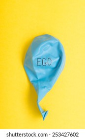 Deflated blue balloon on yellow background with the word ego on it