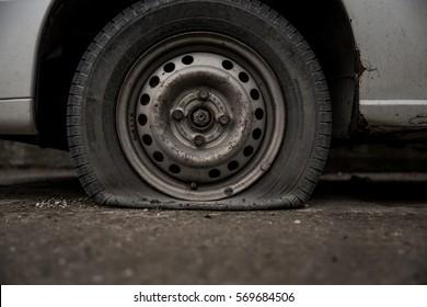 Deflated damaged tyre on car wheel.