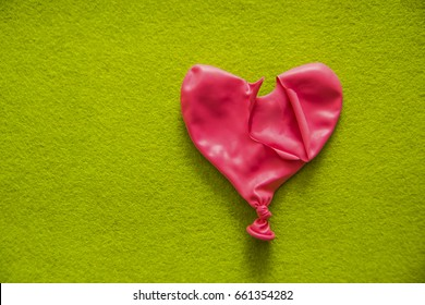 deflated pink red balloon  lie on green texture table. empty copy space for inscription or other objects. Unhappy unrequited love
