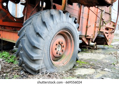 Deflated wheel of the old rusty combine-harvester