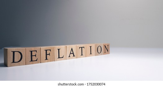 Deflation text from wooden cubes. With spot light in the studio and white background.