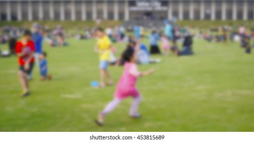 Defocus background of outdoor park with kids and families relaxing and playing.