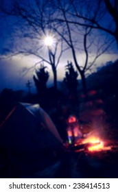 The Defocus Blur of Camping Fire in the Cool Night with Full Moon.