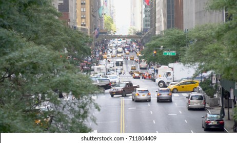 Defocus blur long view down 42nd street in Manhattan. Overhead shot of busy rush hour midtown traffic. Bus, car, personal vehicle occupy street