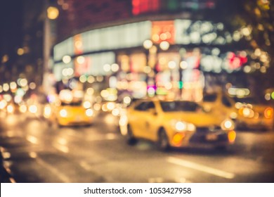 Defocus blur of New York City street scene at night with cars, yellow taxi cabs, lights and buildings