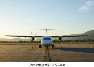 Defocus or Blur of Small Airplane or Aeroplane Parked at Airport.Small Airplane Famous to use Private Airplane.Sunset Light and Mountain View.