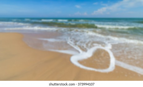 Defocus of heart shape of wave on the beach with blue sky background