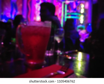 Defocused abstract blurred scene of people enjoy drinking and eating in a dark night club