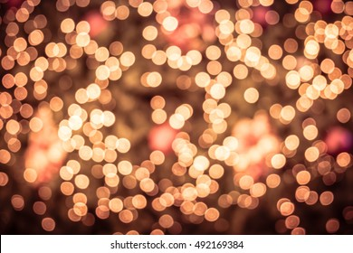 Defocused abstract bokeh circular reflection of Merry Christmas light on gold background. Eve party winter. Happy new year concept.
