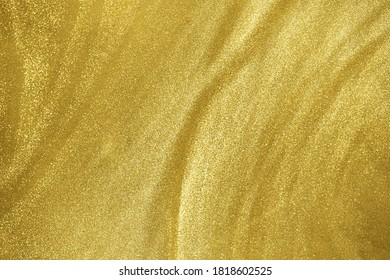 de-focused. Abstract elegant, gold glitter particles flow with shallow depth of field underwater. Holiday magic shimmering luxury background. Festive sparkles and lights.