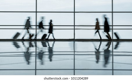 Defocused airport hall with walking travelers. They are going toward to each other in terminal lounge with luggage. Travel concept. Full length