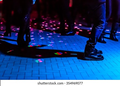 defocused background of a dance floor in a disco club with people dancing under the disco ball blue lights