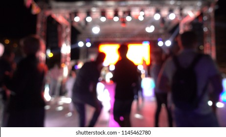 Defocused background. Dance party for children and adults. Silhouettes of dancing people. Multi-colored beams of disco lamps.
