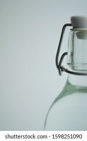 Defocused background. Glass water bottle at gray color backdrop. Zero waste concept packing. Minimalist lifestyle.