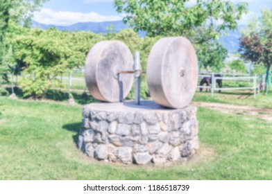 Defocused background with a millstone in the countryside. Intentionally blurred post production for bokeh effect
