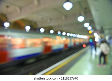defocused background of subway platform and moving train in London UK