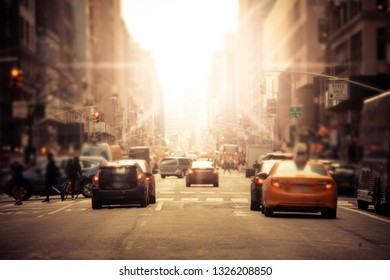 Defocused blur along busy New York City street in midtown Manhattan with cars and anonymous people with sunlight