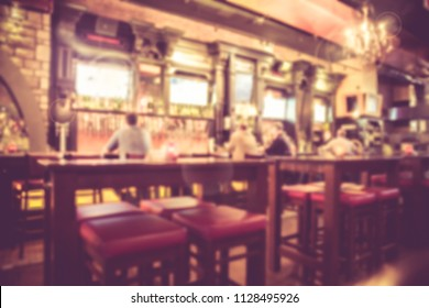 Defocused blur from Irish pub with unrecognizable people at the bar and vintage filter tone.