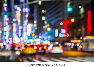 Defocused blur of New York City street in midtown Manhattan at night with cars and lights