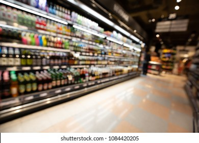 Defocused blur of supermarket shelves with alcohol products. Blur background with bokeh. Defocused image