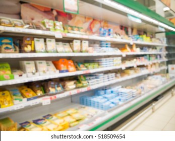 Defocused blur of supermarket shelves with cheese. Blur background with bokeh. Defocused image