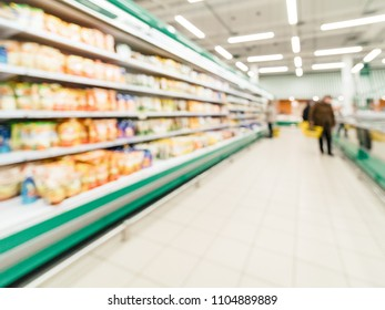 Defocused blur of supermarket shelves with dairy and mayonnaise products in refrigerator. Blur background with bokeh. Defocused image