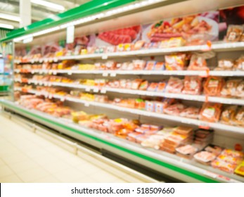 Defocused blur of supermarket shelves with sausages. Blur background with bokeh. Defocused image