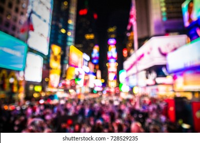 Defocused blur of Times Square in New York City, midtown Manhattan at night with lights and people.