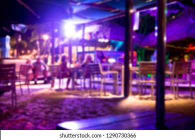 Defocused blur of tropical beach club bar at night with sand, people and purple lights