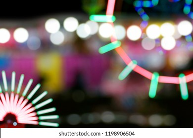 Defocused and blurred image of amusement park at night for background usage.