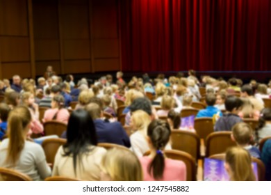 Defocused blurred image of people in the theater or cinema before the performance show.