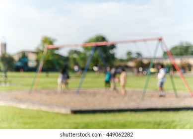 Defocused, blurred motion abstract background of children playground activities in public park at sunset in Houston, Texas. Child swings on modern playground, child and parents doing activity together