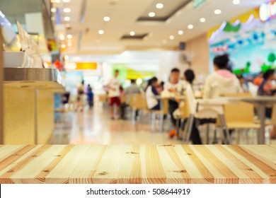 Defocused or blurred photo of food court montage with wood table top use for background.